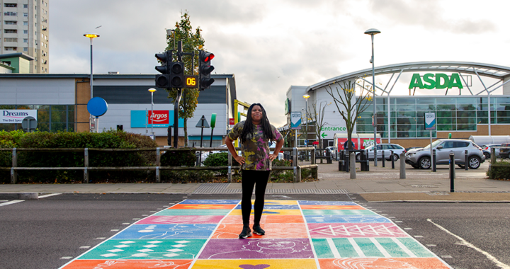 Photo of Kareen Cox standing on the colourful crossing in edmonton green designed by Kareen Cox